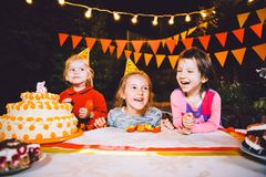 Festa de anos do ` s das crianças Três meninas alegres das crianças na tabela que comem o bolo com suas mãos e que mancham sua ca Imagem de Stock