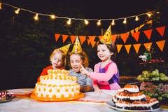 Festa de anos do ` s das crianças Três meninas alegres das crianças na tabela que comem o bolo com suas mãos e que mancham sua ca Foto de Stock Royalty Free
