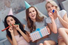 Festa de anos Jovens mulheres nos tampões em casa que sentam-se junto no assoalho que funde na menina dos chifres do partido com  fotografia de stock royalty free