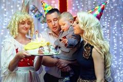 Festa de anos. velas de sopro da família no bolo Foto de Stock