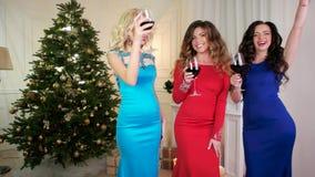 Festa de Natal, um grupo de meninas perto da árvore de Natal no partido de ano novo, álcool da bebida dos vidros de vinho, filme