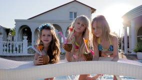 Festa dei bambini della celebrità in piscina, piccola un con i cocktail in mani che spruzzano acqua in stagno, ricco stock footage