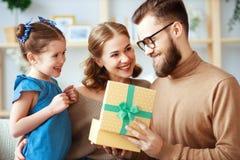 Festa del pap? felice! mamma e figlia della famiglia congratularsi pap? e dare regalo immagini stock libere da diritti