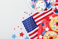 Festa dell'indipendenza fondo felice del 4 luglio con la bandiera americana decorata degli alimenti, delle stelle e dei coriandol Fotografie Stock
