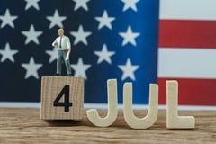 Festa dell'indipendenza U.S.A. con l'uomo d'affari miniatura che sta sul legno Immagine Stock Libera da Diritti