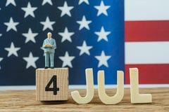 Festa dell'indipendenza U.S.A. con l'uomo miniatura che dà discorso che sta o Fotografia Stock Libera da Diritti