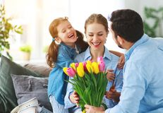 Festa della mamma felice! il padre ed il bambino si congratulano la madre in vacanza immagini stock