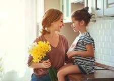 Festa della mamma felice! la figlia del bambino d? a madre un mazzo dei fiori ai narcisi ed al regalo immagini stock libere da diritti