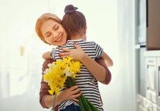 Festa della mamma felice! la figlia del bambino d? a madre un mazzo dei fiori ai narcisi ed al regalo fotografia stock