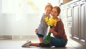 Festa della mamma felice! la figlia del bambino d? a madre un mazzo dei fiori ai narcisi ed al regalo fotografia stock libera da diritti