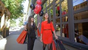 Festa di acquisto, le ragazze sorridenti con gli acquisti in pacchetti indicano le dita al deposito con gli sconti il venerdì ner archivi video