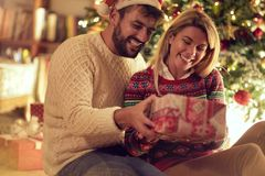 Festa di Natale - uomo allegro e donna con il regalo che godono sulla notte di Natale fotografia stock libera da diritti
