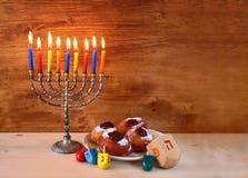 Festa ebrea Chanukah con menorah, ciambelle sopra la tavola di legno retro immagine filtrata Fotografia Stock