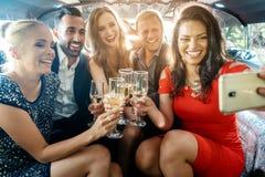 Festa folk i en limo med drinkar som tar en selfie med telefonen arkivfoton