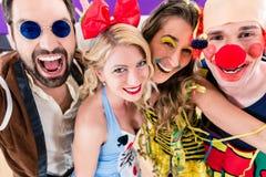 Festa folk som firar karneval eller nya år helgdagsafton Arkivbild