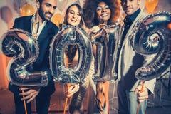 Festa folkkvinnor och män som firar helgdagsaftonen för nya år 2019 royaltyfri bild