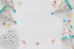 Festa hatten bredvid färgrika konfettier på trätabellen Arkivbilder