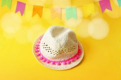 Festa Junina, Brazilian June party greeting card, invitation with straw hat and blurred yellow background with bunting. Flags decoration and bokeh lights Royalty Free Stock Photos
