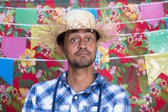 Festa Junina: June Party. People in plaid costume at traditional holiday. Flags and decor in background. Festa Junina: June Party. Happy people in plaid costume royalty free stock image