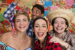 Festa Junina: June Party. People in plaid costume at traditional holiday. Flags and decor in background. Festa Junina: June Party. Happy people in plaid costume stock photos