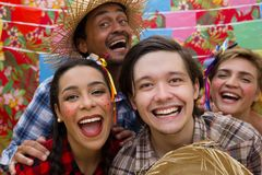 Festa Junina: June Party. People in plaid costume at traditional holiday. Flags and decor in background. Festa Junina: June Party. Happy people in plaid costume royalty free stock photography