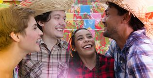 Festa Junina: June Party. People in plaid costume at traditional holiday. Flags and decor in background. Festa Junina: June Party. Happy people in plaid costume stock images