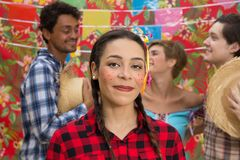 Festa Junina: June Party. People in plaid costume at traditional holiday. Flags and decor in background. Festa Junina: June Party. Happy people in plaid costume royalty free stock photo