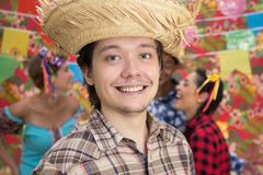 Festa Junina: June Party. People in plaid costume at traditional holiday. Flags and decor in background stock photo