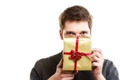 festa Uomo che dà il contenitore di regalo dorato con il nastro Fotografia Stock