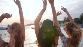Festa vänner som dansar under solnedgång på stranden, flickvänlönelyftarmar upp på sjösidan, unga kvinnor, dansar arkivfilmer