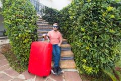Festa, viaggiare e concetto della gente - uomo con la valigia rossa di viaggio che si siede sulle scale la sua casa immagini stock