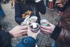 Feste degli amici di Natale che bevono il vino caldo con il marshmello al mercato fotografie stock libere da diritti