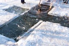 Feste del battesimo ortodosso Un uomo è immerso in un'acqua gelida in un foro sotto forma di incrocio su un fiume immagine stock