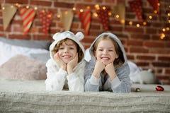 Feste di natale Fratello e sorella che si trovano sul letto in pigiami molli Fotografie Stock