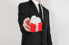 Feste e regali di tema: un uomo in un vestito nero giudica il regalo esclusivo avvolto in scatola rossa con il nastro bianco e ne Fotografia Stock