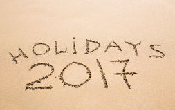 Feste felici 2017 Scritto in sabbia alla spiaggia Festa, Natale, concetto 2017 del nuovo anno Immagine Stock