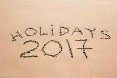 Feste felici 2017 Scritto in sabbia alla spiaggia Festa, Natale, concetto 2017 del nuovo anno Fotografie Stock