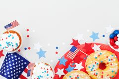 Feste fondo del 4 luglio con la bandiera americana decorata degli alimenti, delle stelle e dei coriandoli dolci Tavola felice di  Immagini Stock