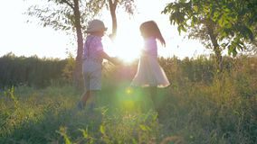 Feste, ragazzino e ragazza del villaggio circondanti insieme al rallentatore tenersi per mano al tramonto archivi video