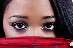 Fester Schuss von attraktiven Afroamerikaner-Frauen-Augen über rotem SH Stockbild