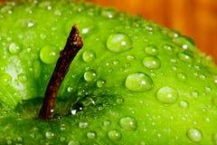 Festes Makro einer grünen Apple-Spitze umfasst in den Wassertropfen nahe stockfotografie