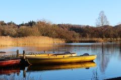 Festgemachte Ruderboote im Wintersonnenschein, Grasmere Stockbild