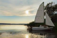 Festgemachtes Boot mit Segel bei Sonnenuntergang, See Lizenzfreies Stockfoto