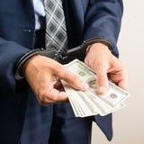 Festgenommener Beamter in den Handschellen, die Dollarbanknoten zählen Concep stockfoto