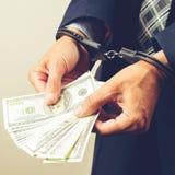 Festgenommener Beamter in den Handschellen, die Dollarbanknoten zählen Concep lizenzfreies stockbild