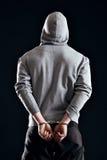 Festgenommener Verbrecher in den Handschellen Stockbild