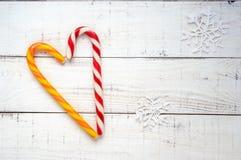 Festins de Noël : cannes de sucrerie lumineuses, dans une forme de coeur sur le blanc un conseil en bois La vue supérieure images stock