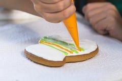 Festins de Noël L'enfant décore le pain d'épice fait maison sous forme de mitaine avec le lustre orange Biscuits de vacances de c Photo stock