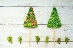 Festins de Noël : lucettes colorées sous forme de sapin sur un conseil en bois blanc Photos stock