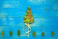 Festins de Noël : lucettes colorées sous forme de sapin sur un conseil en bois bleu Photo libre de droits
